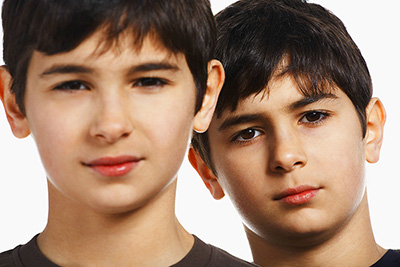 Twin boys (13-15), close-up, portrait